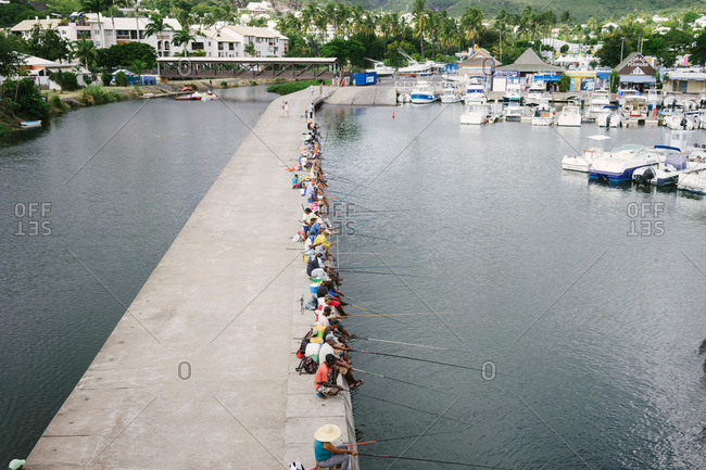 Reunion Island - March 21, 2015: People fishing from the side of a cement pier at Reunion Island