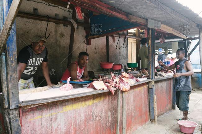 Ambodifotatra, Madagascar - March 23, 2015: Men at a butcher stand in Ambodifotatra, Madagascar