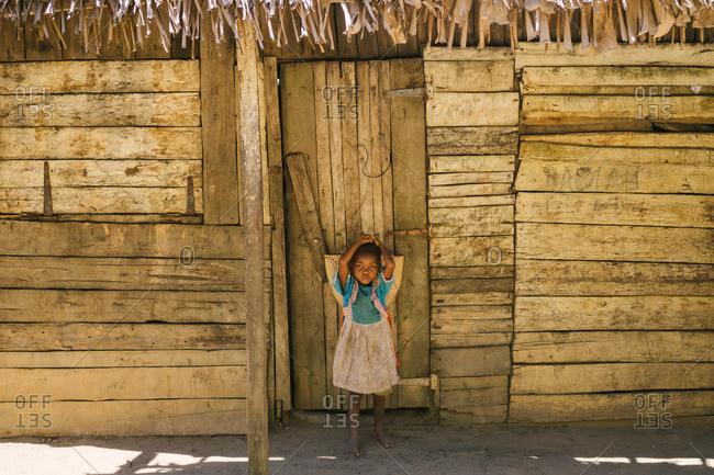 Tolagnaro, Madagascar - March 25, 2015: Little girl standing in front of a doorway in Tolagnaro, Madagascar