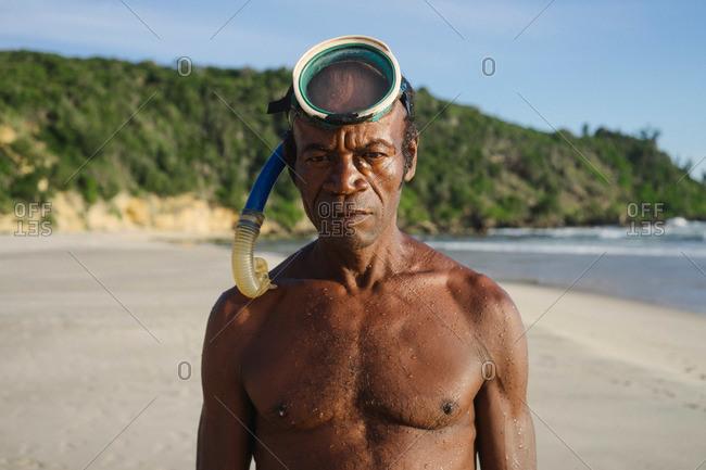 Tolagnaro, Madagascar - March 25, 2015: Man with a snorkel standing on a beach in Tolagnaro, Madagascar