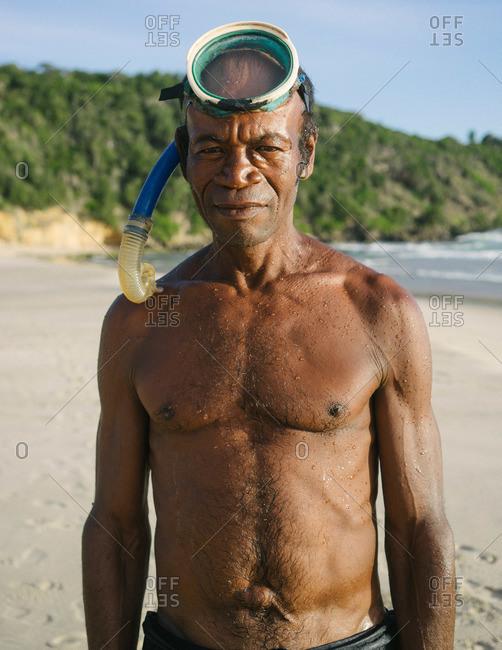 Tolagnaro, Madagascar - March 25, 2015: Fisherman with a snorkel standing on a beach in Tolagnaro, Madagascar