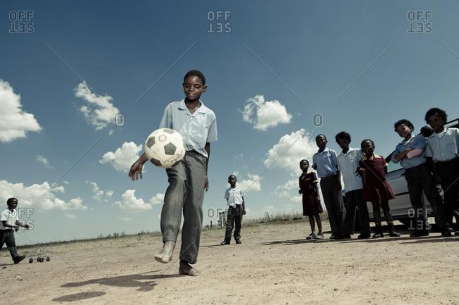 Boy kicking a soccer ball in a school yard