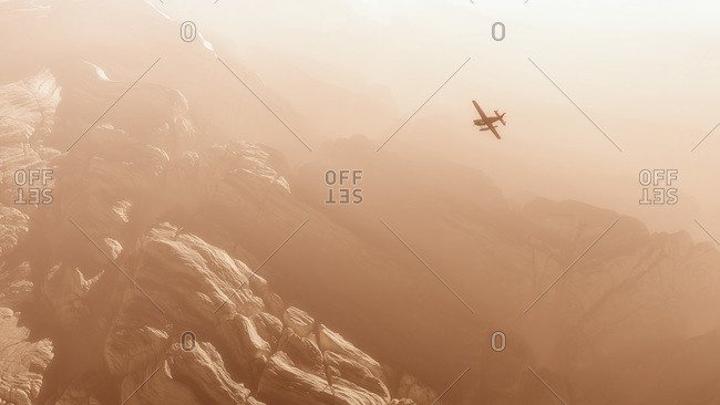 Airplane flying over a rocky mountain range