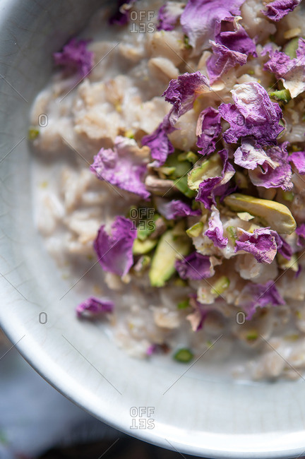 Bowl of oatmeal with purple flowers and pistachios