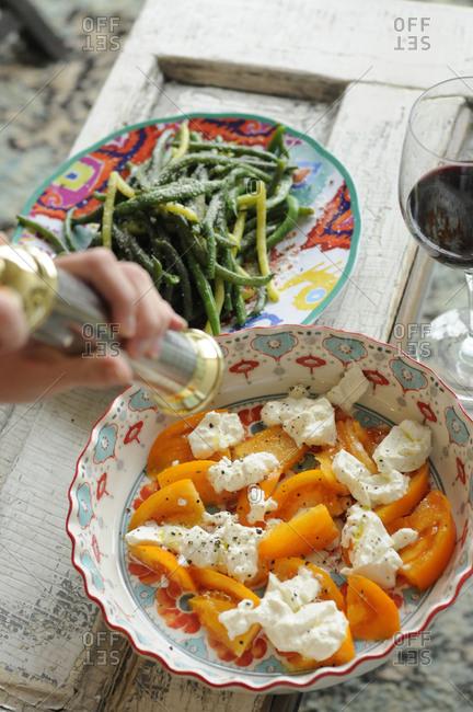 A woman seasons a feta and tomato salad