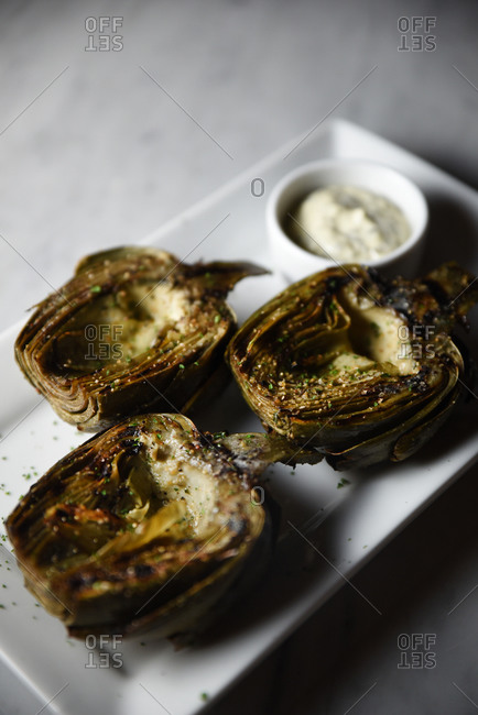 Grilled artichokes topped herbs and garlic
