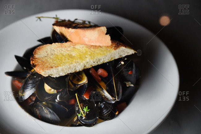 Braised mussels in white wine sauce with tomatoes and garlic