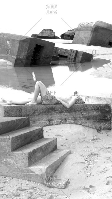 Woman lying among concrete ruins