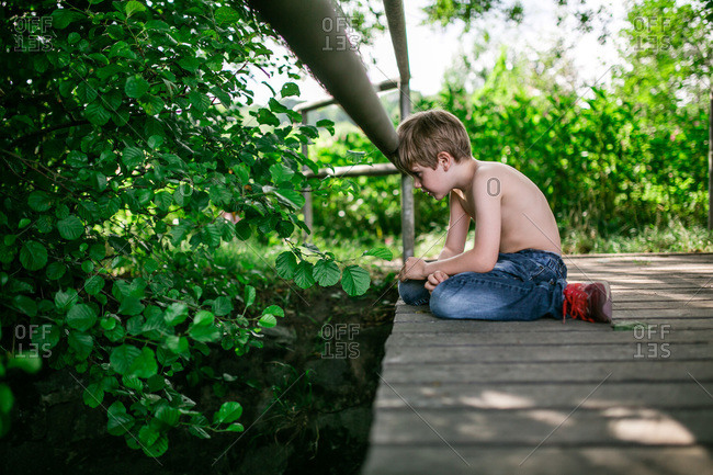 Boy resting his head on the railing of a bridge above a stream