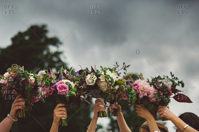 Bridesmaids holding their bouquets up together