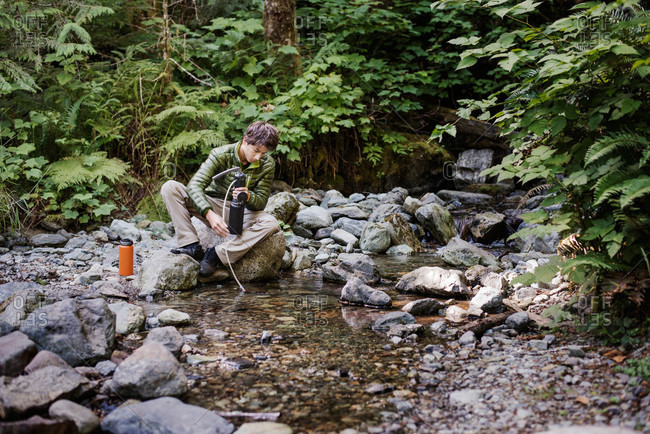 Boy using a water filtration system in a stream