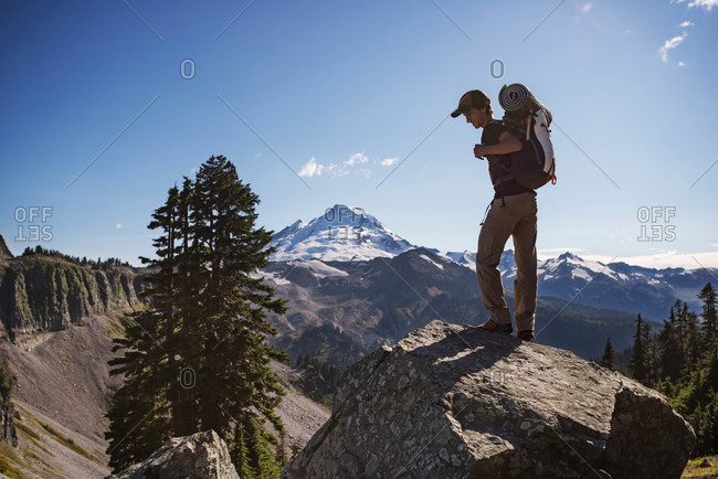 Boy with camping gear standing on a rock in a mountain landscape