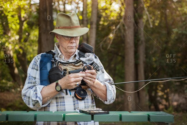 Senior man attaching bait to his fishing line