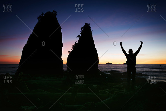 Person making the victory gesture at Rialto Beach in Olympic National Park in Washington