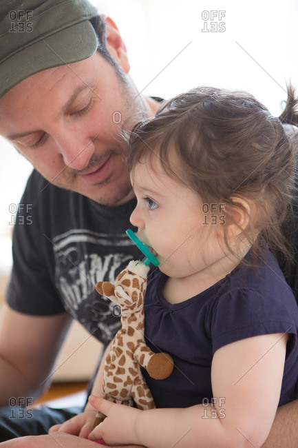 A father holds his daughter who holds a toy giraffe