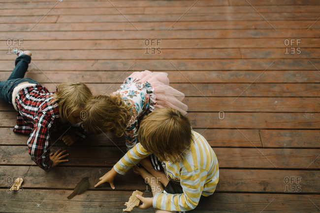 Three children play with a bird