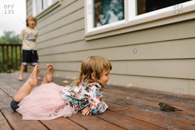 A little girl lays next to a bird on her porch