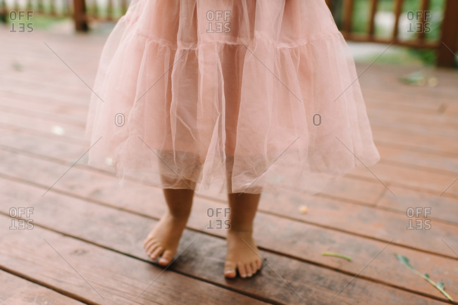 A girl in bare feet in a pink skirt on her porch