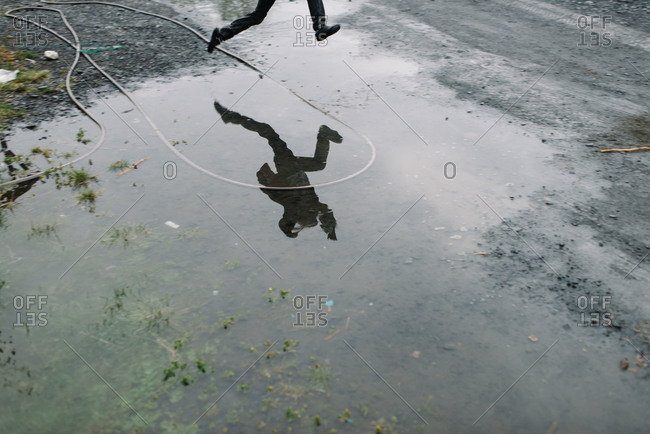 A child leaps over a puddle