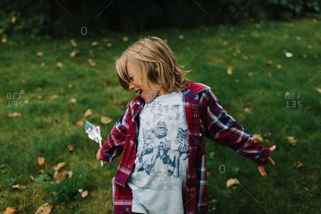 A boy holding a pinwheel spreading his arm