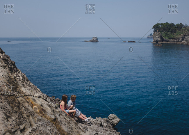 Kids sitting on coastal rocks on the Izu peninsula in Japan