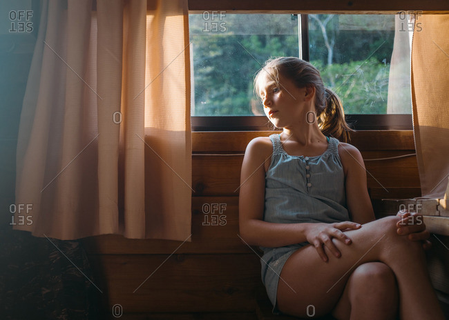 Girl sitting beside a cottage window on the Izu peninsula in Japan