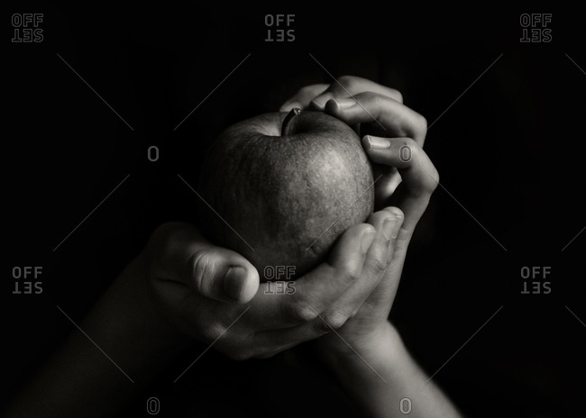 Hands holding an apple