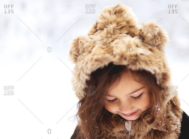 Little girl wearing a furry hood in the snow
