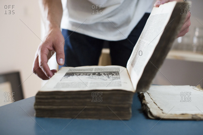 A man paging through a large old book