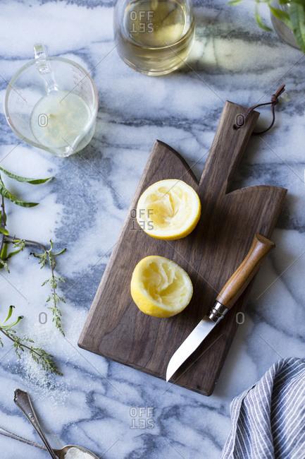 Juiced lemon halves on a cutting board