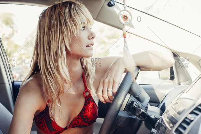 A girl in her car leans on the steering wheel and looks out the window