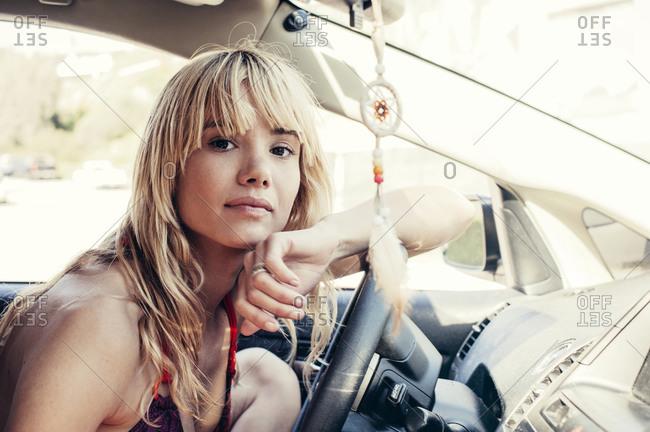 A girl in a bikini leans on her steering wheel