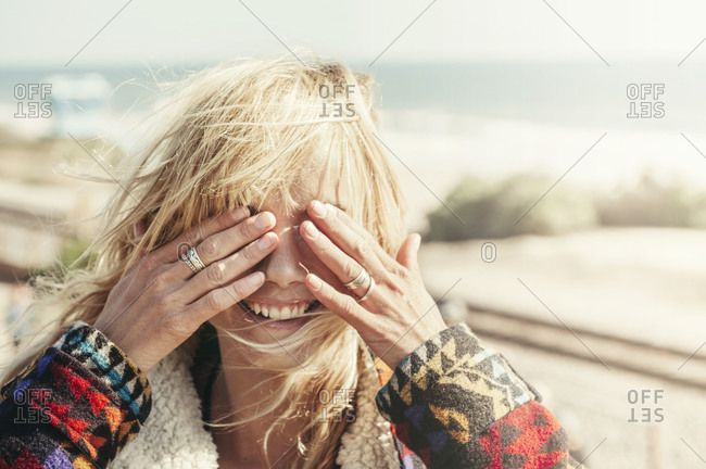 A blonde girl on the beach covers her eyes