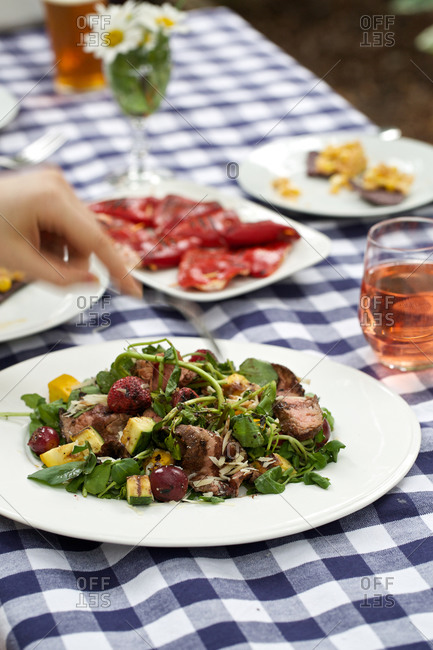 Person eating salad with grilled steak and vegetables