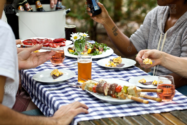 Friends enjoying a barbecued meal outdoors at picnic table