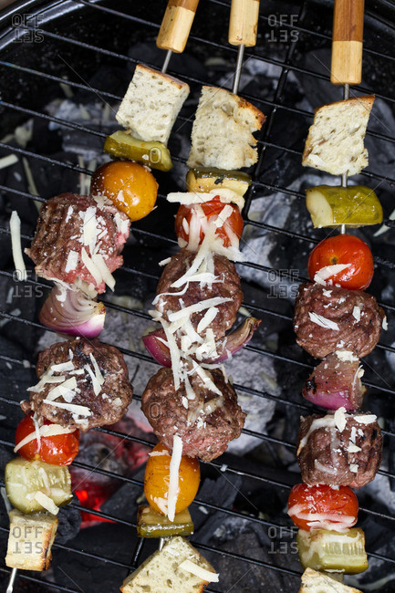 Skewers with meatballs, vegetables and bread on grill