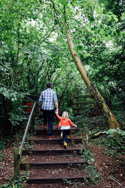 Father and daughter holding hands while walking on steps in the forest