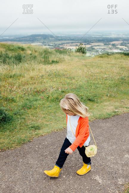 Little girl walking on a mountain trail overlooking