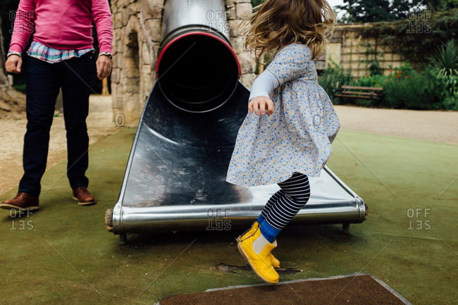 Little girl jumping in front of the end of a metal slide
