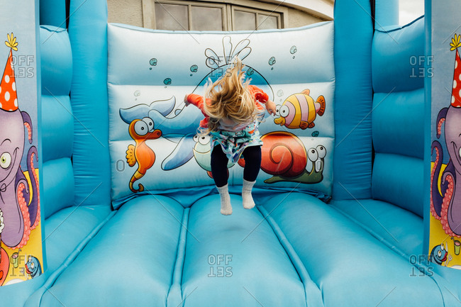 Little girl playing on an inflatable bounce house