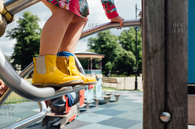 Little girl's rubber boots on playground equipment