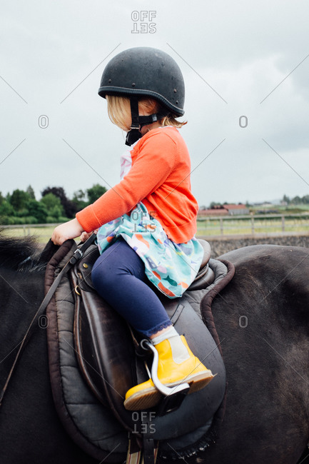 Little girl sitting in a saddle on a horse