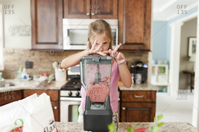 Girl holding down the top of a blender