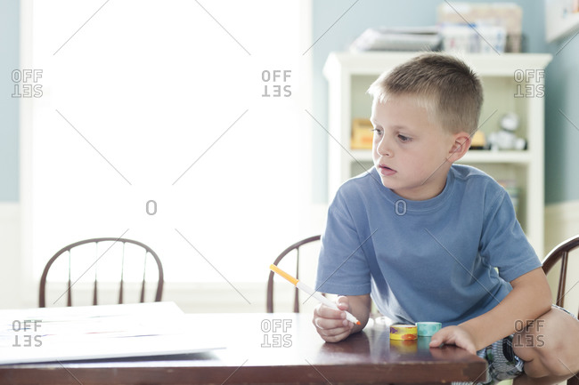 Boy sitting at a craft table holding a marker