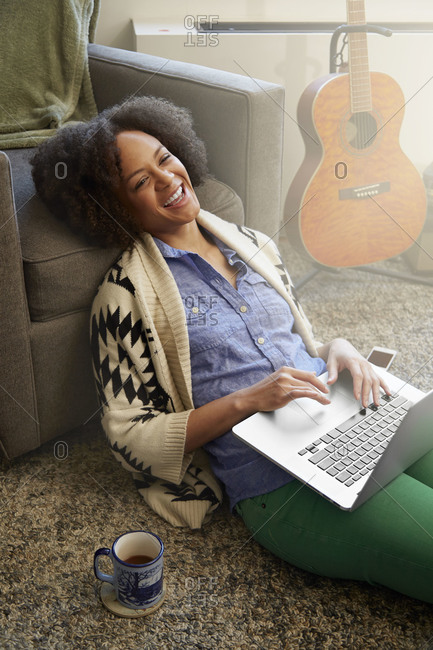 A woman sits on her floor and uses her laptop