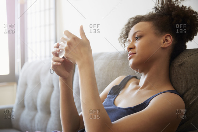 A woman sits on her couch and looks at her phone