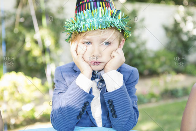 A boy pouts at a birthday party