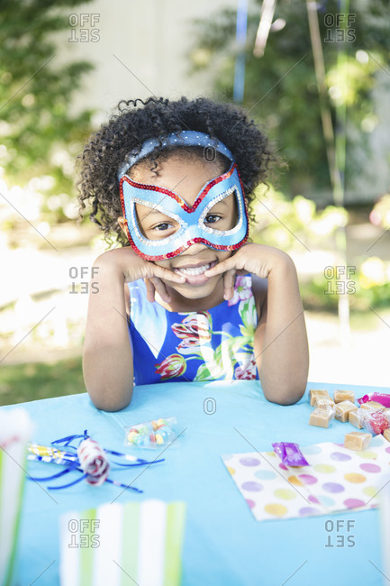 A girl in a mask at a birthday party