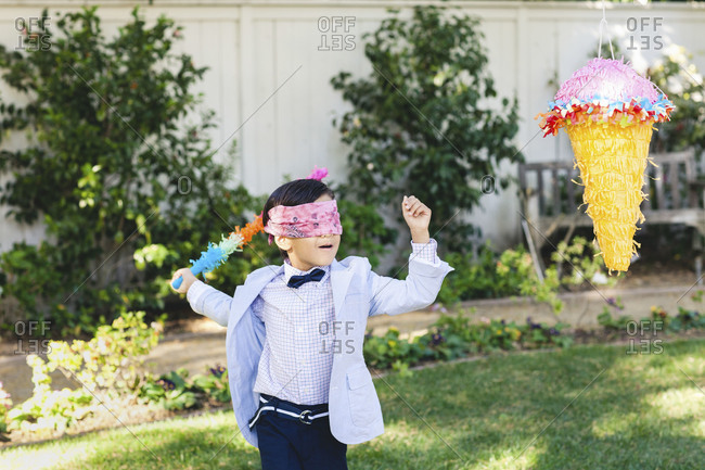 A boy swinging at a pinata at a birthday party