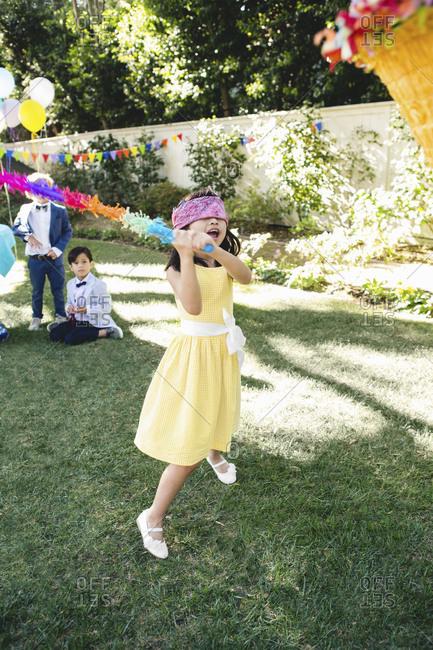A girl swings at a birthday pinata